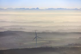 Aerial view of a wind power plant in front of the alpine panorama - Klaus Leidorf Aerial Photography