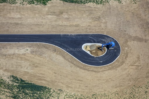 Aerial view of a blue excavator at the end of a cul-de-sac - Klaus Leidorf Aerial Photography