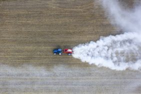 Aerial view of a blue tractor scattering lime dust on the stubble field - Klaus Leidorf Aerial Photography