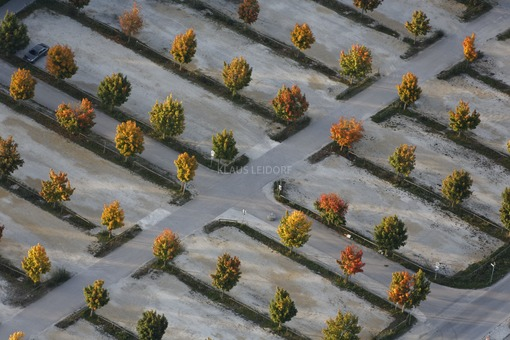 Aerial view of an almost empty parking lot with autumn trees - Klaus Leidorf Aerial Photography