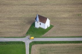 Aerial view of a yellow car in front of the St. Martin's Chapel in Hohenthann-Gatzkofen - Klaus Leidorf Aerial Photography