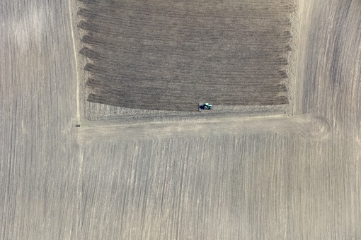 Aerial view of a green tractor working in the field - Klaus Leidorf Aerial Photography