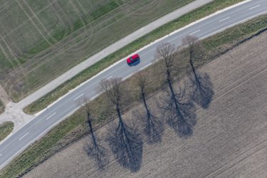 Aerial view of a red car on the country road at five lime trees - Klaus Leidorf Aerial Photography