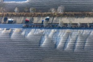 Aerial view of a red car on the wintery country road - Klaus Leidorf Aerial Photography