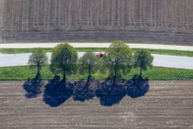 Aerial view of a red car behind a row of trees at the country road - Klaus Leidorf Aerial Photography