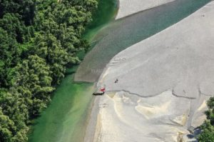 Aerial view of a red towel and rowing boat on the banks of the Lech - Klaus Leidorf Aerial Photography