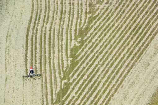 Aerial view of a red tractor working in the field, hay turning - Klaus Leidorf Aerial Photography