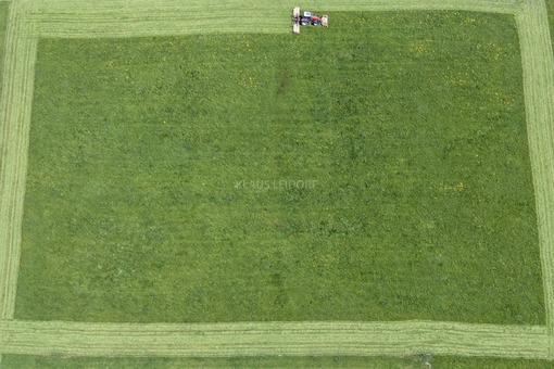Aerial view of a red tractor at the meadow mowing - Klaus Leidorf Aerial Photography