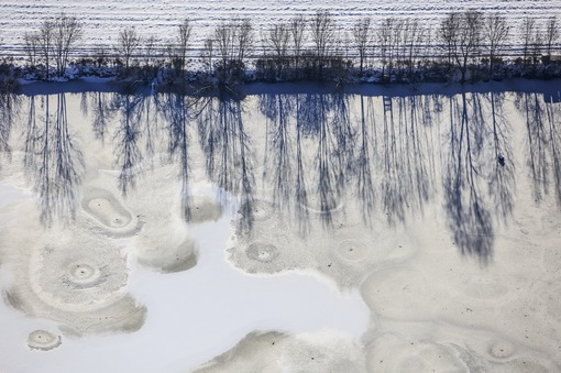 Aerial view of a frozen gravel pond with shady trees on the bank - Klaus Leidorf Aerial Photography