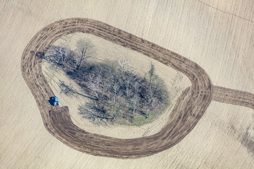Aerial view of a tree island in the field, which a farmer is circling with his blue tractor while harrowing - Klaus Leidorf Aerial Photography