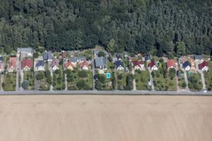 Aerial view of a settlement of detached houses at the edge of a forest with large front gardens - Klaus Leidorf Aerial Photography