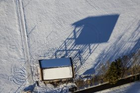 Aerial view of a shadow-casting field barn - Klaus Leidorf Aerial Photography
