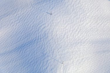 Aerial view of a snow-covered field on which two electricity pylons stand - Klaus Leidorf Aerial Photography