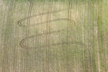 Aerial view of a sinusoidal tractor track on a field - Klaus Leidorf Aerial Photography