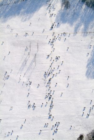 Aerial view of many people walking across the snowy meadow in the English Garden in Munich - Klaus Leidorf Aerial Photography