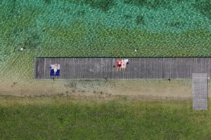 Aerial view of a wooden landing stage on which 3 young people are sunbathing - Klaus Leidorf Aerial Photography