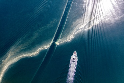 Aerial view of the passenger ferry MS Barbara, which crosses a strip of pollen on the lake Chiemsee - Klaus Leidorf Aerial Photography