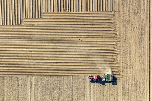 Aerial view of a planting action on a dusty potato field - Klaus Leidorf Aerial Photography