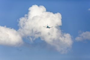 Aerial view of an overtaking jet airplane in front of the clouds - Klaus Leidorf Aerial Photography